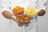 Chef holding bowls of dried fruits mid section