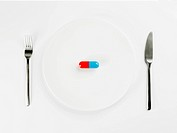 Single pill on white plate close_up, directly above
