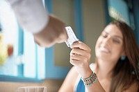 Woman giving credit card to man close_up