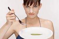 Mid adult woman eating single mangetout