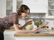Mid adult woman reading newspaper while having breakfast at kitchen counter