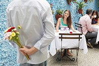 Man holding bunch of flowers behind his back, woman waiting at table