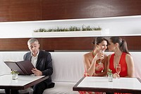 Man listening to two women whispering in restaurant