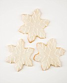 Three snowflake sugar cookies with decorative icing.