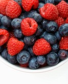 Bowl of mixed blueberries and raspberries on white background