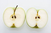 Still life of sliced green apples on white background
