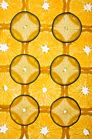 Orange and lime slices arranged in design on white background