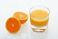 Halved orange and glass of orange juice on white background