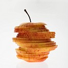 Red apple sliced and stacked against white background