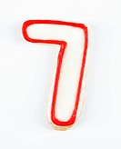 Sugar cookie in the shape of a number seven outlined in red icing
