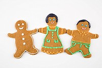 Three male and female gingerbread cookies holding hands