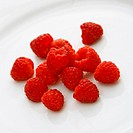 Red raspberries on white background