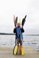 Senior man holding oars on jetty