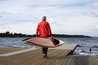 Senior man carrying a kayak (thumbnail)
