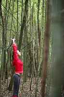 Young woman stretching in forest (thumbnail)