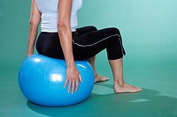 Mature woman sitting on Swiss ball close_up