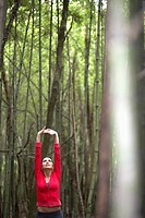 Young woman stretching in forest