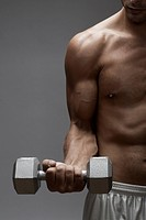 Mid adult man lifting dumbbell midsection