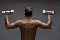 Mid adult man lifting dumbbell rear view