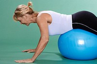Mature woman exercising on Swiss ball (thumbnail)