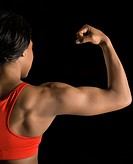 Back view of African American woman flexing muscular bicep