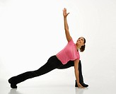 Mid adult multiethnic woman wearing exercise clothing holding yoga pose and smiling