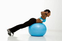 Profile of African American young adult woman working out with exercise ball.
