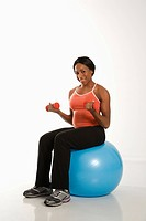 Smiling African American young adult woman sitting on exercise ball holding dumbbells