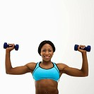 African American young adult woman raising dumbbells over head and smiling at viewer