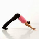 Side view of mid adult multiethnic woman wearing exercise clothing in downward dog yoga pose