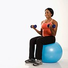 African American young adult woman sitting on exercise ball holding dumbbells