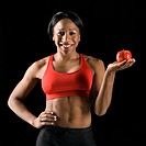 Smiling African American young adult woman holding apple with hand on hip