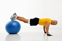 Side view of mid adult multiethnic man doing pushups while balancing on blue exercise ball.