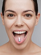 Vitamin pill on young woman's tongue