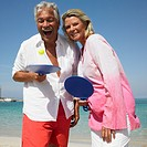 senior couple on beach playing with bat and ball