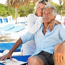 senior couple on beach on sunloungers