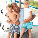 Grandfather and grandchildren 6_8 on beach by windsurfer