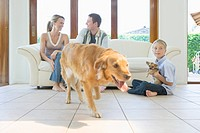 Family with dogs in living room, parents sitting on couch, smiling