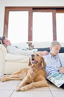 Father and son with dogs in living room, father in headphones lying on couch and son reading magazine on floor