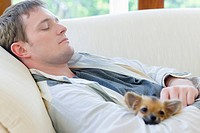 Man with Chihuahua sleeping on couch