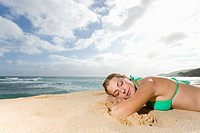 Young Woman Sleeping on Beach with Her Face Down