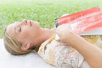 College Girl Lying on Grass with Holding Book