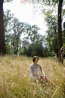 Caucasian woman sitting on grass, Side View