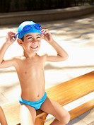 Boy in swimming trunks adjusting goggles (thumbnail)