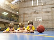 Boys lying on floor near basketball portrait (thumbnail)