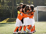 Children in soccer uniforms hugging