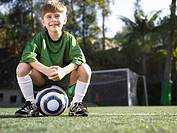 Boy sitting on soccer ball portrait, low angle view