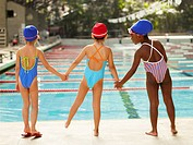 Three girls holding hands by swimming pool rear view