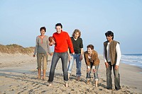 Five people with football standing on beach portrait