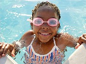 Young girl wearing swimming goggles in pool portrait